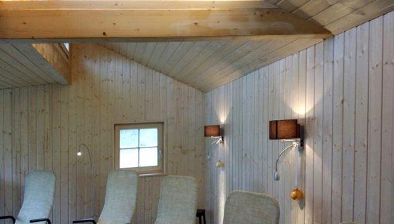 Wandleuchten mit Lichtauslass nach oben und unten in gemütlichem Innenbereich eines Hallenbades mit Sauna