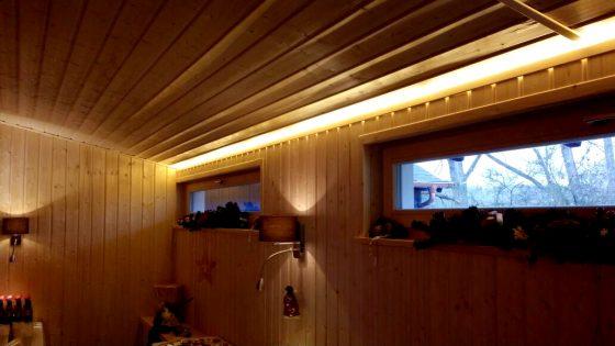Stimmungsvoll ausgeleuchtete Sauna deren Wandleuchten mit Lichtauslass nach oben und unten strahlen und ein zusätzliches Deckenlicht das sich über die komplette Breite zieht