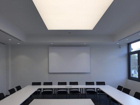 Mit Deckenleuchten und einer LED-Lichtdecke ausgeleuchteter Konferenzraum bei Tageslicht