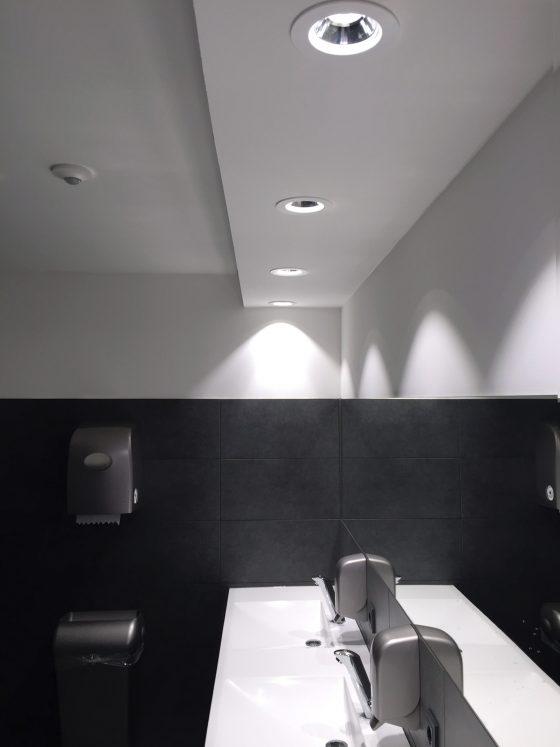 Runde Deckenleuchten über zwei Waschbecken in einem schwarzweiß gehaltenen Badezimmer