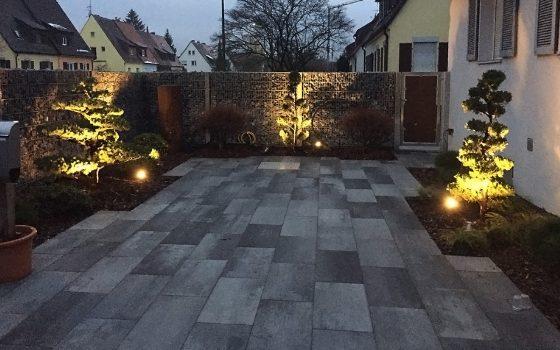 Stimmungsvolle Gartenwegbeleuchtung: Bodenstrahler in gelbem Licht mit Ausrichtung auf diverse Objekte