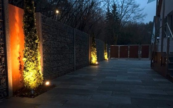 Stimmungsvolle Gartenbeleuchtung: Bodenstrahler in gelbem Licht mit Ausrichtung auf mehrere Nadelbäume am Wegesrand