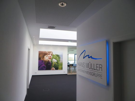 Mit Deckenleuchten und LED-Lichtdecken ausgeleuchteter Gang in einem Bürogebäude