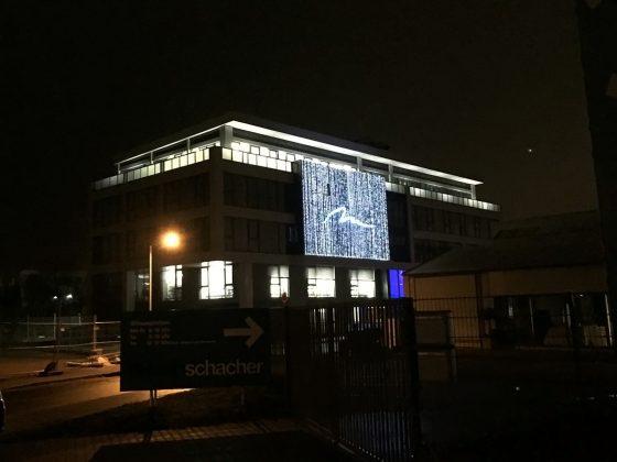 Nachtaufnahme: LED-Teppich an Bürogebäudenfassade und zusätzliche Bodenlampen auf der Dachterrasse